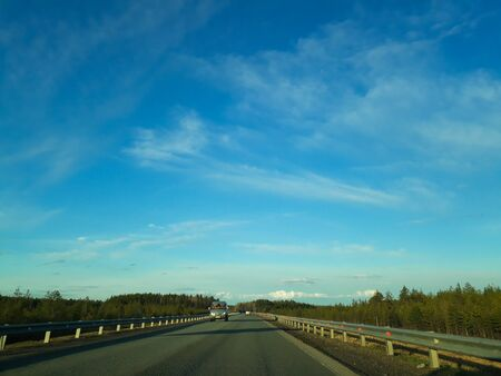 A road or highway leading to the horizon. View from the car window. Northern dim summer, blue sky with white clouds. Journey, the way home.