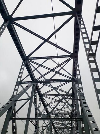 Metal construction of the railway bridge with the rising middle part for the passage of ships. View from below from the car window. Architecture, design elements