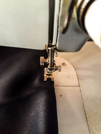 Stitching, vertical photo - the foot of a sewing machine on a black cloth, a straight line. Handicrafts, sew yourself