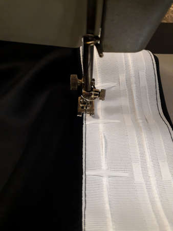 We sew curtains - sewing curtain tape to the fabric. Blackout with your own hands. Handicraft. Business. Textiles for the house Banco de Imagens