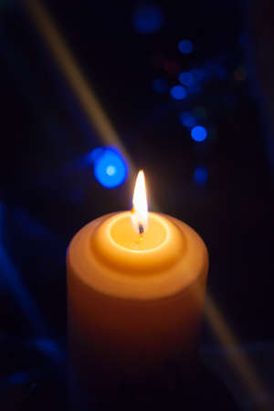 A large candle burns against the background of a garland with shining lights. Vertical photo, defocus. Mystic esoteric romance divination mood christening Christmas carol setcers