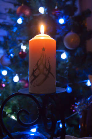 A large candle burns against the background of a garland with shining lights. Vertical photo, defocus. Mystic esoteric romance divination mood christening Christmas carol setcers Stock Photo
