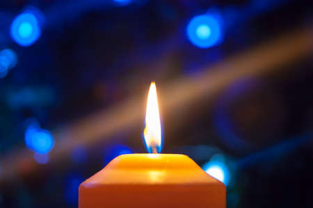 A burning orange candle on a dark background with blue lights - a Christmas New Years eve divination mystic esoteric romance love mood. Horizontal photo, side, focus or defocus. Фото со стока - 155818887