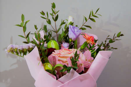A delicate bouquet of different flowers in a light pink wrapper stands on a gray background. Horizontal photo.