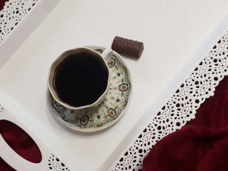 Morning coffee in a small porcelain cup with a graceful pattern and showcolade candy on a white tray in bed
