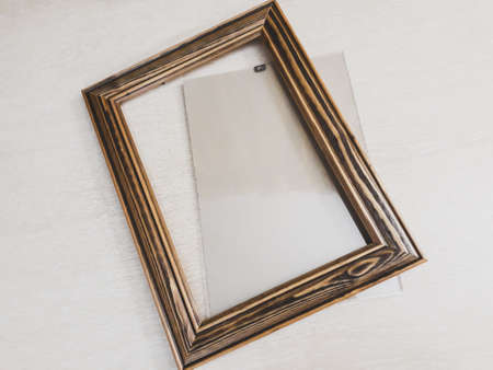 Frame of dark wood for needlework on a light background, horizontal photo