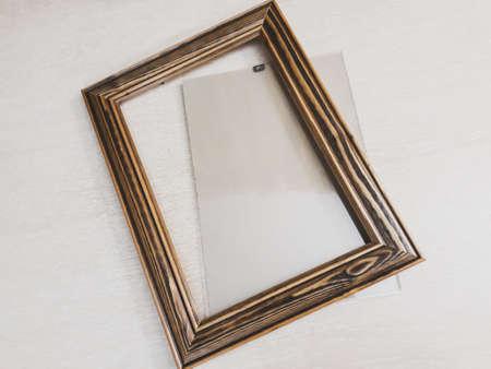 Frame of dark wood for needlework on a light background, horizontal photo Фото со стока