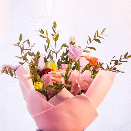 A delicate bouquet of different flowers in a light pink wrapper stands on a light background in a home setting. Square photo, top view. Gift, recognition, love, joy, happiness