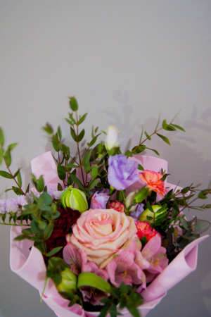 Delicate bouquet of different flowers in a light pink wrapper on a gray background. Vertical photo.