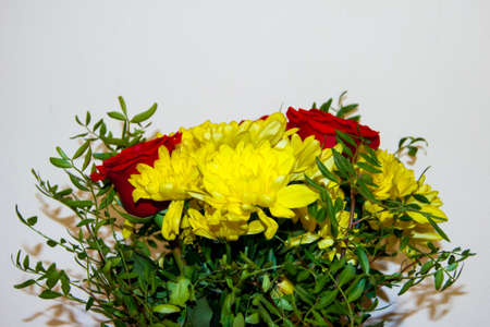 A bouquet of flowers made of red roses and yellow chrysanthemums without packaging stands in a vase against the white wall. The flowers are large. A gift, a declaration of love. Holiday.