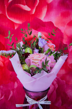 A delicate bouquet of different flowers in a light pink wrapper stands against a colorful pink wall in a home setting. Vertical photo.