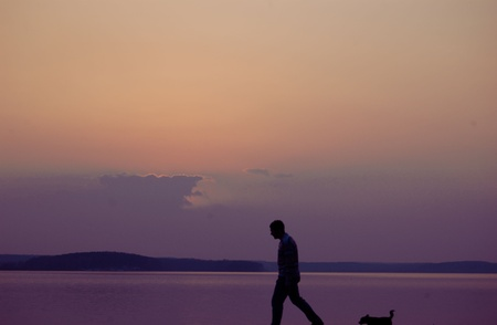 silhouette of a man with a dog at sunset Stock Photo - 9067399