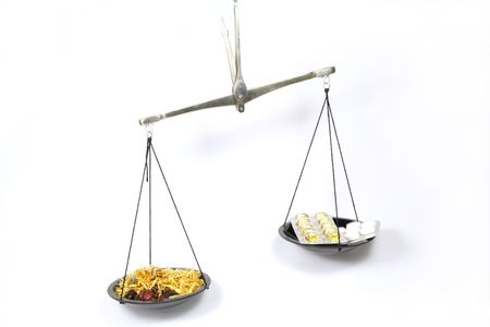 weigher: Scales symbolizing Homeopathy is more effective than traditional medicine Stock Photo