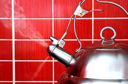 Koken Polished water koker op rode achtergrond van het naast elkaar plaatsen  Stockfoto