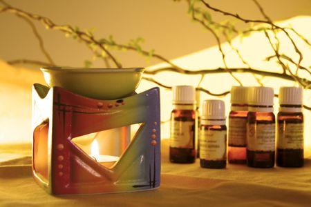 Aromalamp met brandende kaars en flessen met olie aromatherapie