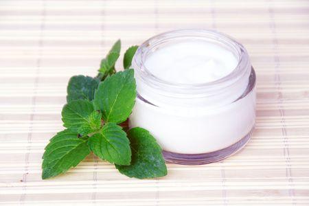 Cosmetische gezicht room fles en groene bladeren Stockfoto