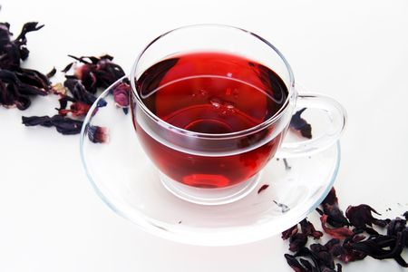Glass Cup of Karkadeh Red Tea with Dry Flowers Stock Photo