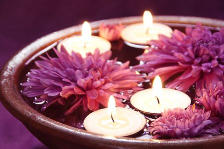 Aroma Bowl met kaarsen en bloemen in violet Stockfoto