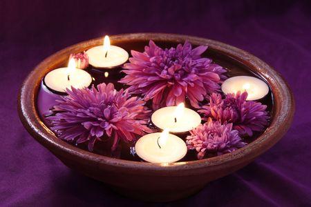 Aroma kom met kaarsen en bloemen in Violet Stockfoto