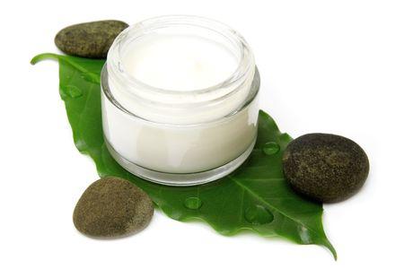 Natuurlijke vocht inbreng ende crème op blad met stenen geïsoleerd
