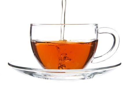 Gieten van thee in glas Cup. Caption = Losse op wit Stockfoto