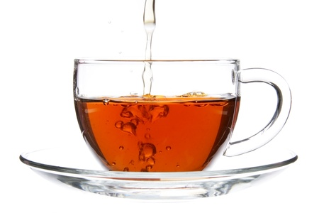 Pouring Tea into Cup with Splash Isolated photo