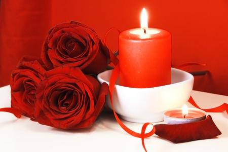 Brandende kaarsen en boeket van rode rozen