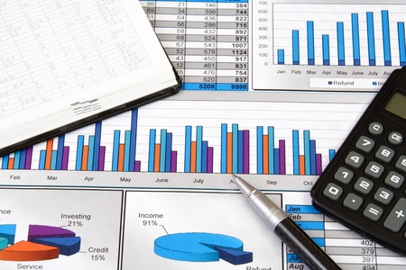 Report in Charts and Graphs with Calculator, Notepad and Pen photo