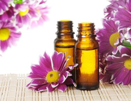 Flessen etherische olie en roze bloemen Stockfoto