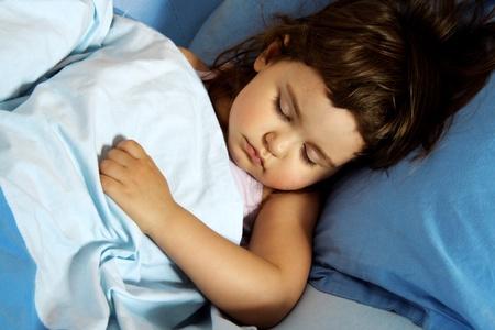 ni�o durmiendo: Ni�a dormir tranquilamente en la cama Foto de archivo