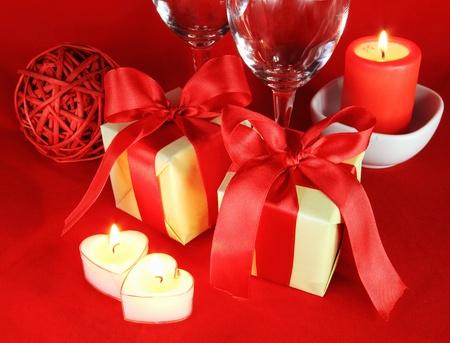 Romantische omgeving met kaarsen en glazen over rode stof Stockfoto