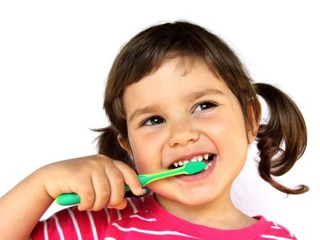 Weinig glimlachend krullend meisje het borstelen tanden portret