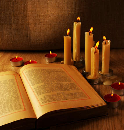 Open Old Book and Burning Candles Still Life photo