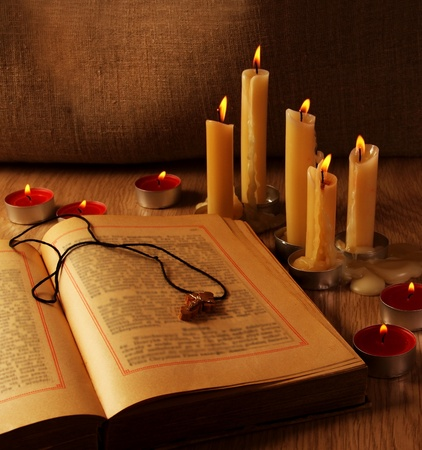 burning paper: Wooden Cross over Open Old Testaments Still Life Stock Photo