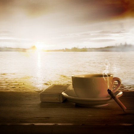 Loneliness. Coffee and Cigarette Burning Down against Sunset Stock Photo