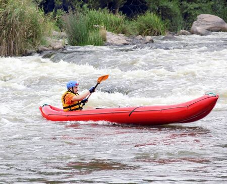 Young Man in Raft on Extreme White Water Stream photo
