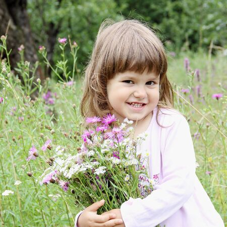 Playful Smiling Girl with Bunch of Wild Flowers photo