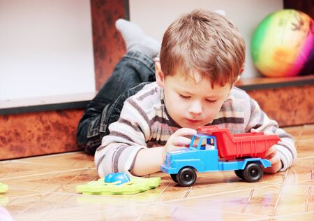 toy truck: Little Boy Playing with Toy Truck in Nursery
