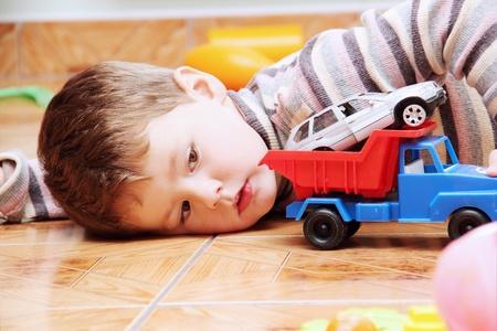 Kleiner Junge spielt mit Spielzeug-Auto Truck schließen Standard-Bild