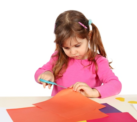 Little Child Girl Making a Cutout with Scissors photo