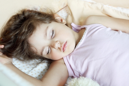 Child Girl Asleep in Her Bed on Back Stock Photo
