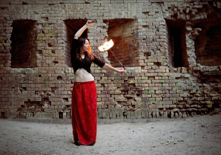fire show: Young Girl Twisting Burning Poi on Fire Show Stock Photo