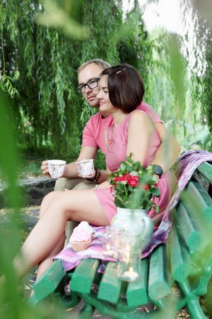 Lovers Drinking Tea on Bench Outdoors Picnic photo