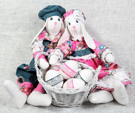 Two Easter Handmade Bunnies with Decorated Eggs in Basket photo