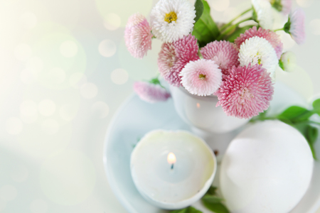 easter candle is burning: Easter holiday pastel card with daisies in eggcup Stock Photo