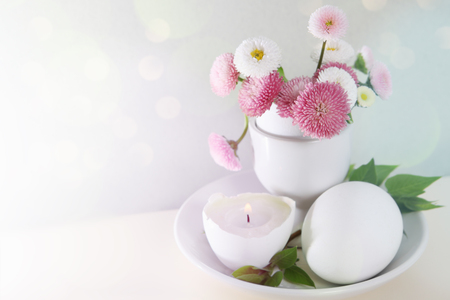 easter candle is burning: Easter holiday daisies in eggcup card with space for text Stock Photo
