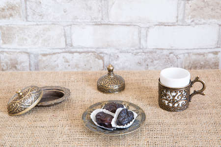 Turkish coffee with dried dates, brick wall background.