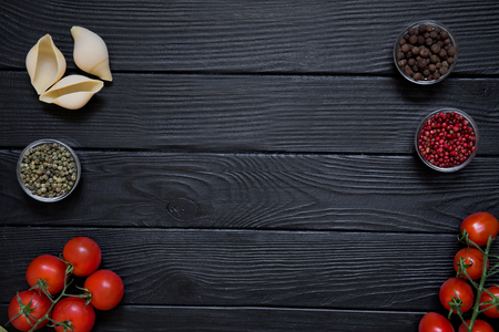 Fresh ingredient for Italian cuisine dishes on black wooden table background. Big conchiglie, red cherries tomatoes and different kinds of spice, reg, green and allspice pepper. Copy space.