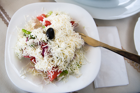 Bulgarian, serbian and macedonian traditional cuisine Shopsky salad or shopska salata with tomatoes, cucumbers, paprika, onion and goat cheese brynza.