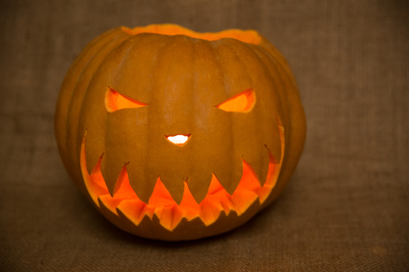 Halloween symbol jack-o-lantern. Scary carved pumpkin with burning candles. Copy space.